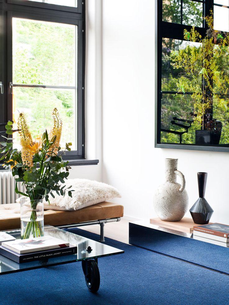 Oscar properties - Bryggeriet - Industriverket #oscarproperties  living room, design, art, chairs, red chairs, interior, design, tree house, blue carpet, flowers, fikus, windows, industrial windows, pots, krukor, konst
