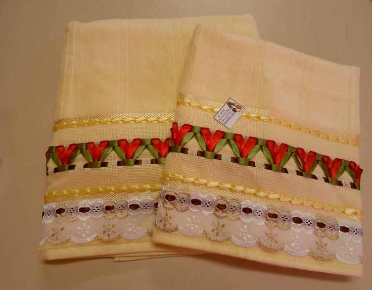 Jogo de toalhas amarelas trançadas com fitas de cetim, formando lindas tulipas vermelhas, composta por 1 (uma) toalha de banho e 1 (uma) de rosto. Enfeitada com bico de cambraia branco e marrom claro.
