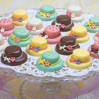 Our tea hats begin with a shortbread cookie topped with delicious layers of moist cake. Next they are covered with chocolate and adorned with a hand cut flower fashioned from chocolate fondant. Variet