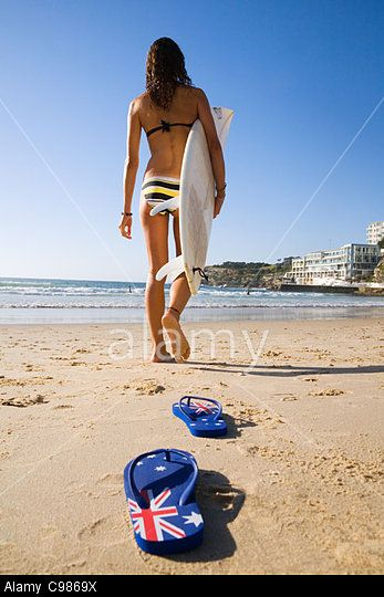 Surfer girl carrying surfboard and walking towards water at Bondi Beach. Sydney, New South Wales, Australia