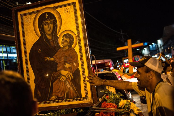 Brazil- 85% religious Catholics touch an icon of the Virgin Mary and Jesus Christ as it is taken along with the World Youth Day (WYD) Cross that in 1984 Pope John Paul II entrusted the youth of the world, across Rocinha shantytown in Rio de Janeiro on July 18, 2013. The Pope is due in Rio for the July 22-28 Catholic WYD, an event expected to attract two million people from around the globe.
