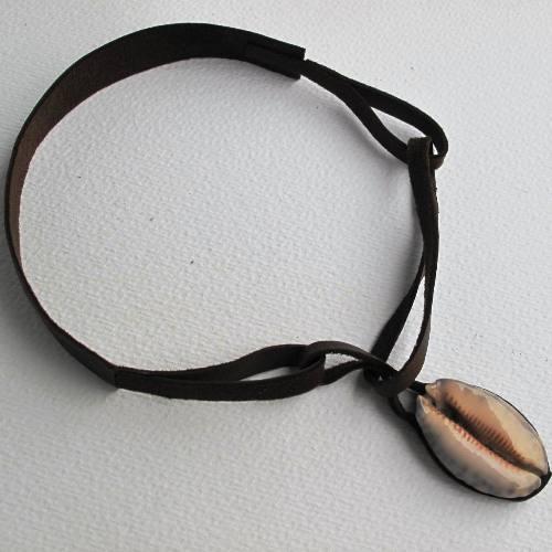 Collar de ante con una pequeña caracola cortada cubierta de una pieza de madera por detrás. El collar se abrocha por delante, utilizando la concha como peso. Cuesta 14 euros.