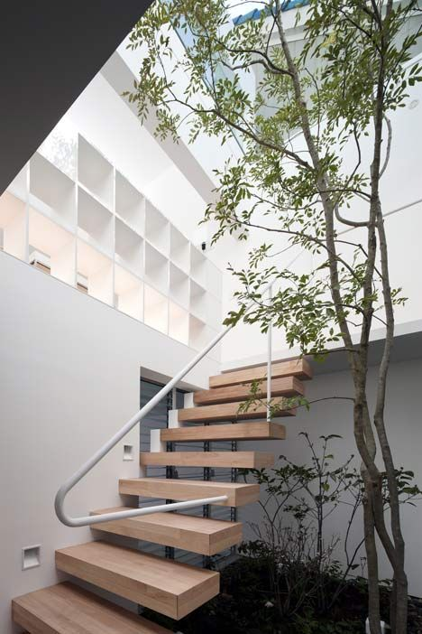 Japanese studio UID Architects has completed a 2-storey house in Fukuyama. Instead of adding windows to the facade, there are a series of skylights & clerestory windows to bring daylight.The indoor garden occupies a double-height space at the centre of the residence & also acts as a lightwell for the entrance lobby at the front of the ground floor. A grid of bookshelves provides balustrade around the edge of the courtyard, which is also the location of a wooden staircase connecting the 2…