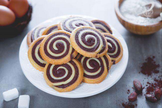 I biscotti girandola sono degli sfiziosi dolcetti di pasta frolla bicolore, cacao e bianco che insieme creano un originale effetto visivo!