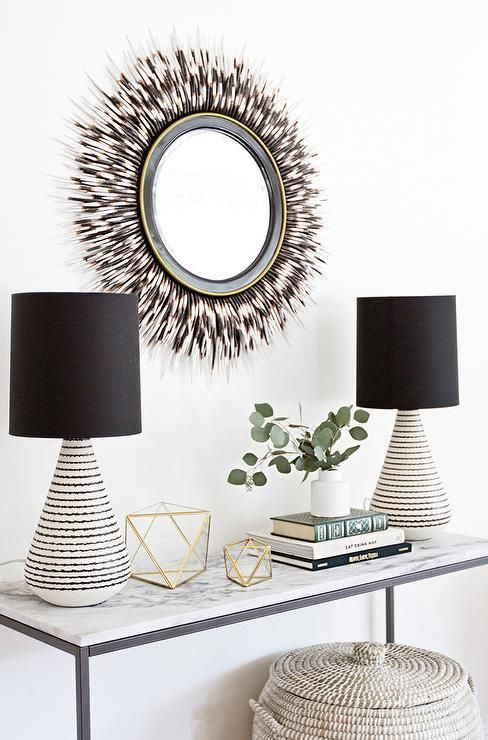 Gorgeous foyer features a bronze and marble console table, West Elm Box Frame Console Table, topped with black and white lamps by Crate & Barrel placed under a Janice Minor Porcupine Quill Mirror.