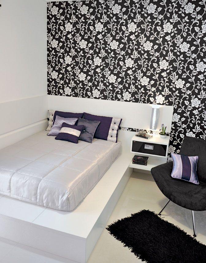Na iluminação foi utilizada uma luminária de luz indireta central. Foi colocada também uma arandela no painel da cabeceira da cama para leitura. O papel de parede e as almofadas em tons lilás, dá um toque de cor. A predominância do branco deixa o quarto iluminado e aparentemente maior. Além disso, destaca as peças escuras.