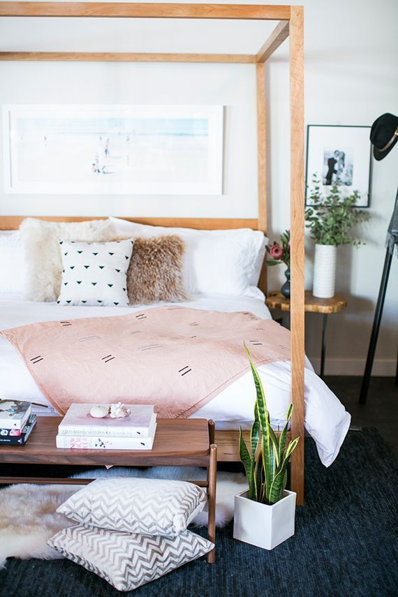 Pretty bedroom. Wood tones, white and blush pink with dark floors and greenery.