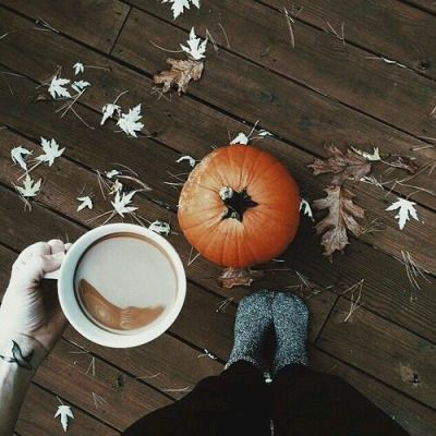 All the details of autumn assemble in one picture: pumpkin, coffee, woolen socks and dead leaves.