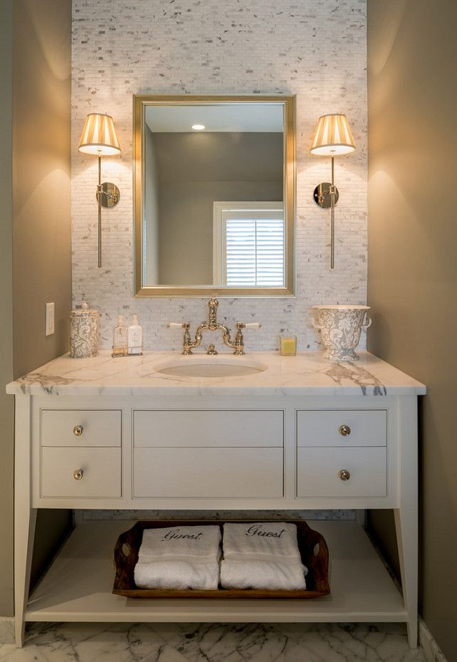 A custom made vanity painted in a crisp white paint is perfectly paired with a marble countertop