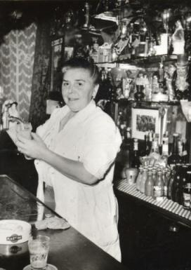 1950's. Bet van Beeren behind the bar at Cafe 't Mandje on the Zeedijk in Amsterdam. The café is considered to be the first gay bar in the Netherlands and one of the first in the world. It was opened in 1927 by Bet, herself a lesbian. After her death in 1967, her sister Greet continued the café until it closed in 1982. Just before her death in August of 2007, she took the initiative to have the bar reopened.  #amsterdam #1950 #Mandje #Zeedijk #BetvanBeeren