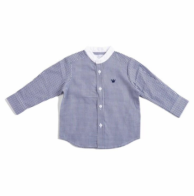 """Camisa para bebe niño confeccionada en algodón 100%, con diseño de cuadritos tipo """"vichy"""" en azul oscuro y blanco. Cuello tipo """"mao"""" en color blanco y mangas largas. Se abotona al frente y del lado izquierdo tiene un bordado con la coronita de EPK bordada en azul oscuro."""