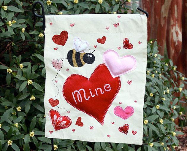 White flag with bee and hearts on it with bush behind