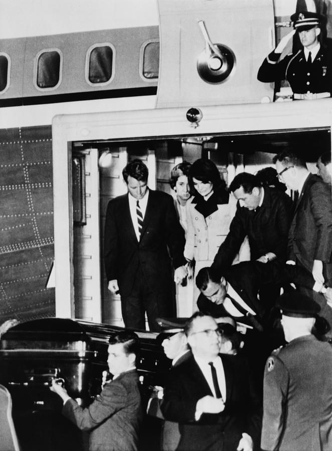 John Kennedy's Coffin. Robert Kennedy holds Jacqueline Kennedy's hand as they watch the body of the assassinated President removed from Air Force One to an ambulance. Andrews Air Force Base, Nov. 22, 1963.