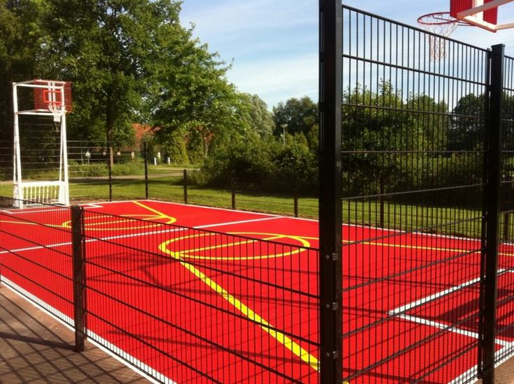 Het eindresultaat, 7,5 x 15 meter. Wit gepoedercoate basketbal-voetbaldoelencombinatie. Geplaatst op asfalt, en voorzien van rode vloercoating en sportbelijning. 7,5 x 15 meter, contactgeluidsarm.