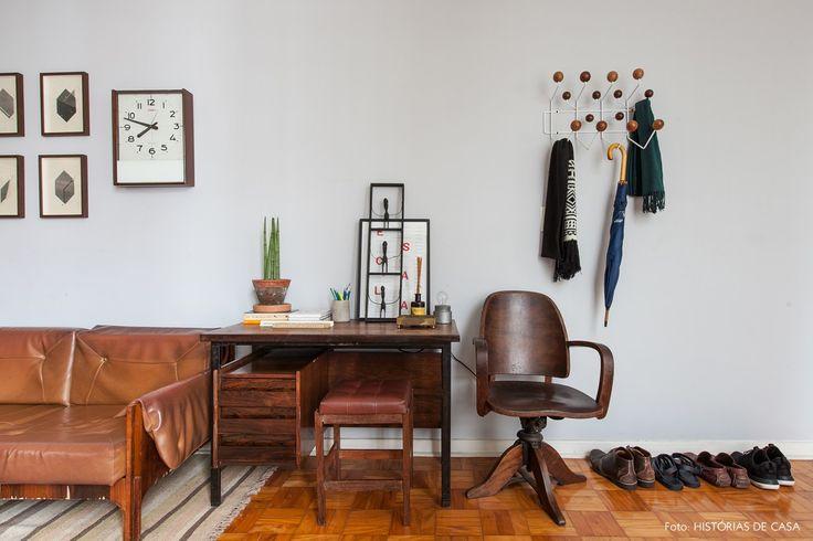 Sala de estar tem parede pintada de cinza claro, sofá, escrivaninha e cadeira vintage.