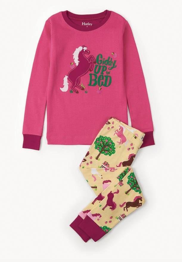 2-delige meisjes pyjama Pony van het kinderkleding merk Hatley. Een pyjama uit 2 delen met een roze t-shirt. Op de t-shirt staat een afbeelding van een pony die op haar achterpoten recht staat, met een groene geborduurde tekst erbij : Giddy up to bed. De ronde hals en de uiteinde van de mouw is afgewerkt in het paars.  De pyjama broek heeft een gele kleur, en is voorzien van een all over print van verschillende kleuren pony's met boompjes en appelen erbij.