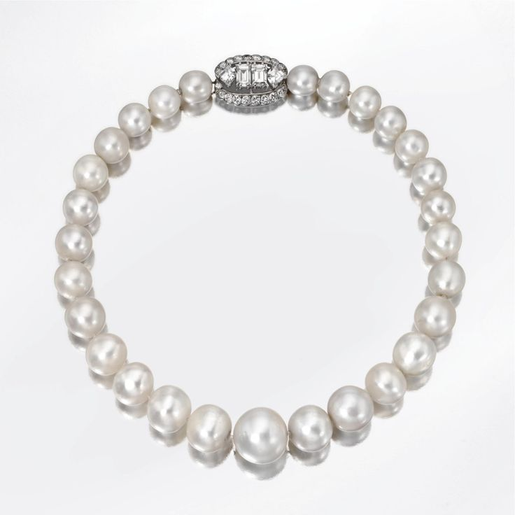 Duchess of Windsor Natural Pearl Necklace by Cartier  A Single Strand Natural Pearl and Diamond Necklace, Cartier, Paris Composed of 28 natural pearls graduating from approximately 16.8 to 9.2 mm., completed by an oval clasp set with 2 emerald-cut diamonds weighing approximately 2.00 carats and 2 fancy-shaped diamonds weighing approximately 1.00 carat, bordered by 20 small round diamonds weighing approximately .70 carat, length 14 inches, clasp signed Cartier, Paris. Photo courtesy of…