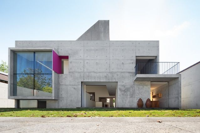 """The influence of Luis Barragán is evident in the rear elevation's large, cruciform window of the living space and the pop of """"Mexican pink"""" revealed behind a shutter."""