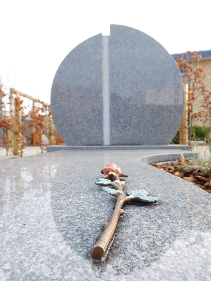 Bronzen roos op een gedenksteen met ronde vormen. De gedenksteen is gemaakt van een lichte soort graniet.