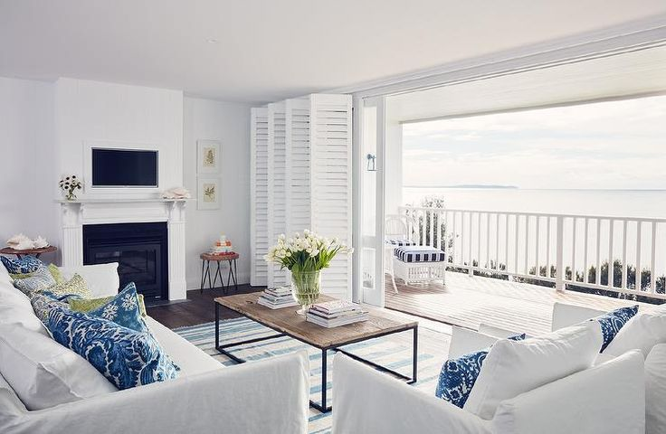White and blue coastal living room features a white slipcovered sofa and accent chairs lined with a collection of blue pillows facing a wood and iron industrial coffee table atop a blue stripe rug and bi-fold plantation shutters over sliding glass doors.