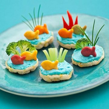 These savory bites, assembled from rice cakes, cream cheese, and fresh veggies, make a wholesome classroom treat or afternoon munchie.                  Tint a small tub of plain whipped cream cheese with blue food coloring, then spread dollops onto mini rice cakes. Cut herbs and vegetables as shown (we used chives, red bell peppers, broccoli, and celery) and press them into the cream cheese. To curl the celery, cut slits into one end of a trimmed stalk and place it in a bowl of ice water…