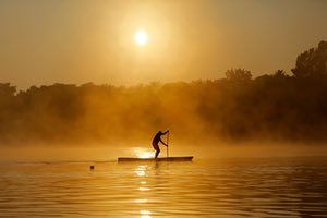Johannesburg, South Africa: A rider paddles on the Emmarencia Dam as mist rises off the water