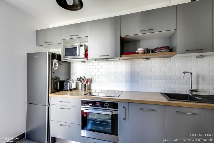 Une cuisine moderne, en longueur, avec meubles gris et plan de travail en bois.