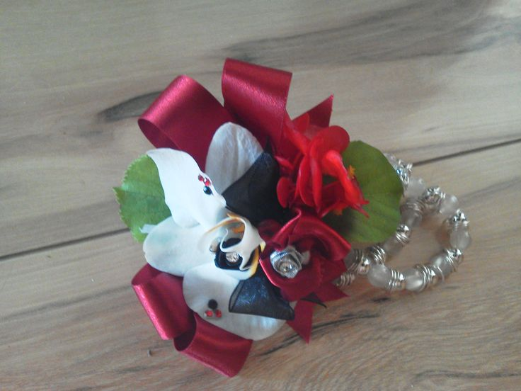 Our white Orchid lady's corsage with red ribbon was created to perfectly match a beautiful deep red dress.