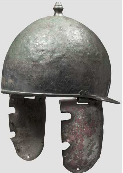Roman legionary's helmet of the Montefortino/Buggenum type,  1st century A.D. Cast and embossed bronze, retaining much of its silver-colored white metal plating (tin-plating). Hemispherical skull with a stud-shaped top knob. Perforated neck protector slightly sloping, with reinforcement bulges on the rim. These also trim the rest of the helmet. Perforated cheek pieces on the sides with double-pinned hinges, 34 cm high. Private collection, from Hermann Historica auction