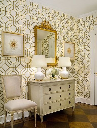This entryway features a gilded mirror, beautiful chest with Greek key detail, a Louis chair, a pair of classic white porcelain lamps, and a modern, graphic touch thanks to the spectacular Cowan and Tout wallpaper and checkerboard wood floors.