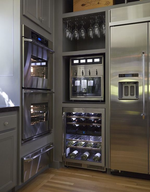 Wine lovers' kitchen features stainless steel double wall oven and warming drawer framed by gray cabinets adorned with glass hardware adjacent to cubbies filled with an under cabinet wine glass rack above a refrigerated wine dispenser atop a wine cooler with separate temperature zones specifically for white wine and red wine.