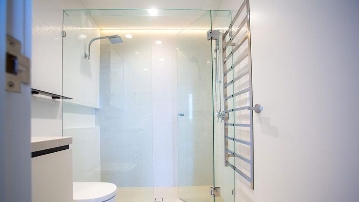 Simple and sophisticated bathroom with frame less shower screens