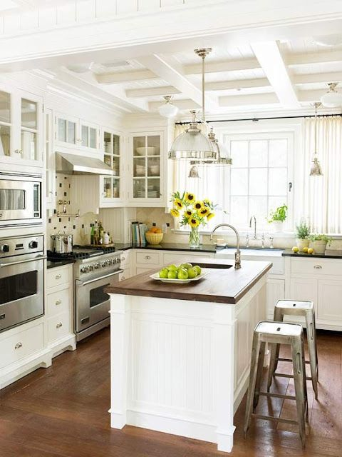 White kitchen, wood counter on island, wood floors, coffered ceiling, window coverings