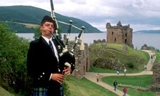 A piper plays the bagpipes in front of the ruins of Urquhart Castle by Loch Ness.  http://www.visitscotland.com