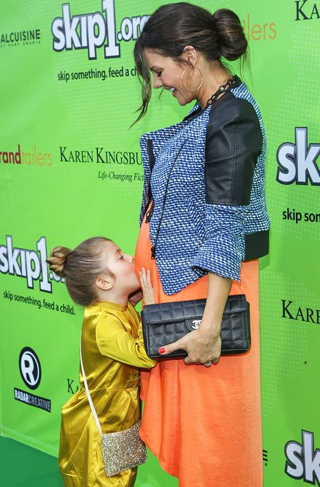Ali Landry's daughter, Estela, kisses her mom's baby bump on the red carpet