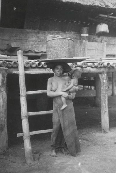Indonesia, Sumatra ~ Portret van een Karo Batak vrouw met haar kind op de arm en een mand op het hoofd Date 1910-1930 Source Tropenmuseum