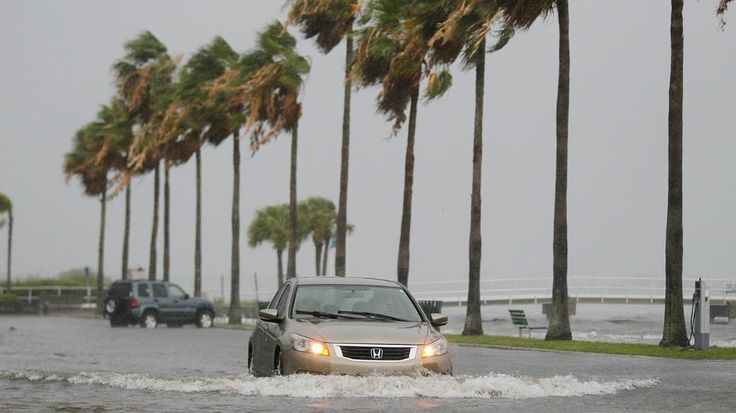 A vehicle moves through water from Tropical Storm Colin in Gulfport, Fla., Monday, June 6, 2016. A large portion of Florida's western and Panhandle coast was already under a tropical storm warning when the National Hurricane Center announced that a swift-moving depression had become a named storm.