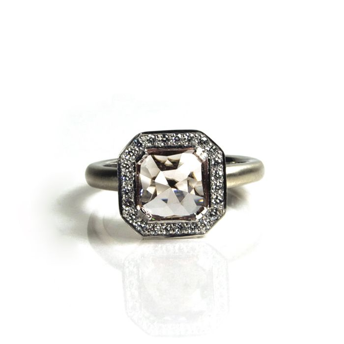 A Valentine Proposal: Asscher Cup Ring. Setting holds an 8mm Asscher cut center gemstone (price does not include center stone), surrounded by twenty-four 1.3mm white diamonds for a TCW of .24 cts. Face of ring is 12.5mm across with a 3mm wide half-round band. The gem sits high on the hand in this unusual cup setting.  Our favorite gems for this setting are Morganite and White Sapphire.