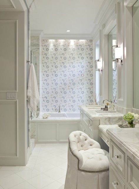 bathrooms - light gray paneled walls sage green walls white tufted vanity chair marble top drop down light gray vanity flanked light gray bathroom cabinets