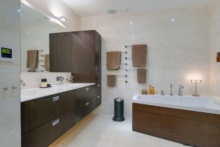 Badrummet har samma ljusa kakel/klinker på vägg som golv men i blankt utförande på vägg och i matt på golv. Det är utrustat med måttbeställt handfat i Corian med underskåp i Wenge trä från Lidhults, vägghängt WC från Duravits Philippe Starck serie samt dusch. Matadorgatan 2 i Halmstad.
