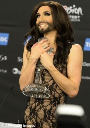 Conchita Wurst, clutching the winner's trophy after triumphing at Eurovision...