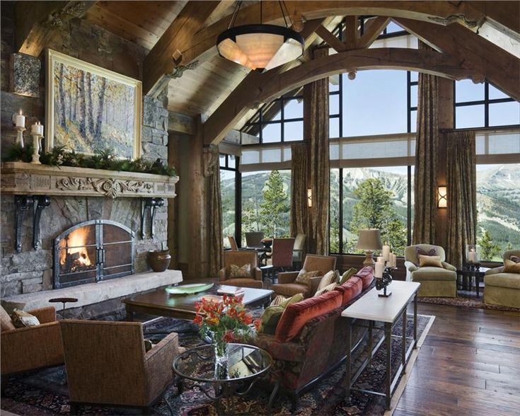 rustic great room with trusses large stone fireplace and wall of