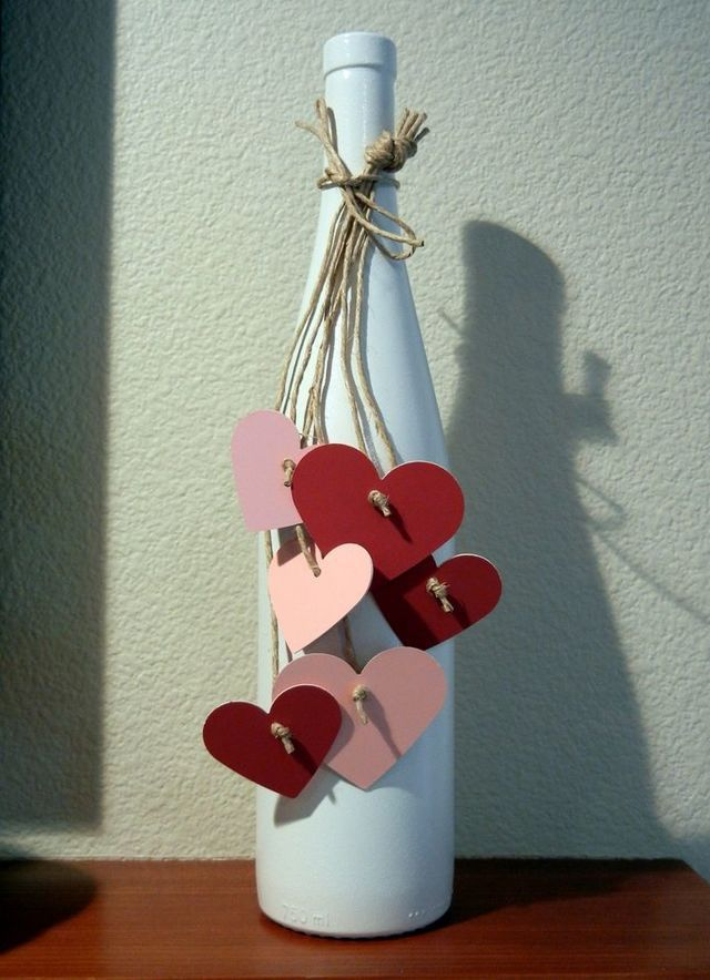 Spray paint a wine bottle with white paint and attach hearts with twine