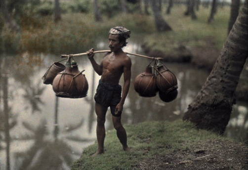 The First Color Photos of Bali, Indonesia in 1920s, 1928, Bali, Indonesia --- A Balinese man carries pots with a potent drink to be sold at market --- Image by Franklin Price Knott