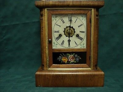 """Clock stands 13"""" tall and the face is 5"""" square. The following information is printed on the inside of the clock: """"Marine Lever Time Pieces For Ships, Steamboats, Locomotives and Dwellings. Octagon E"""