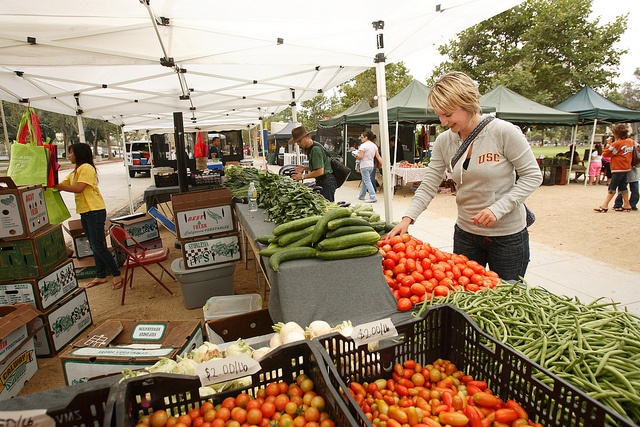 """Students at the University Park campus have ready access to seven nearby farmers' markets, in addition to the """"Trojan Fresh"""" market held regularly in Alumni Park throughout the academic year. Here, Johanna Mulder from the Netherlands, a visiting researcher at the USC Gould School of Law, selects Roma tomatoes in the booth run by Xiong Farms of Fresno, CA, at the Exposition Park farmers' market, just south of campus."""
