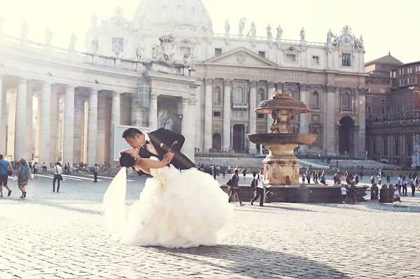 the happy couple kissing in Roman square - photo by Rochelle Cheever, Rome Weddings Photography via junebugweddings.com