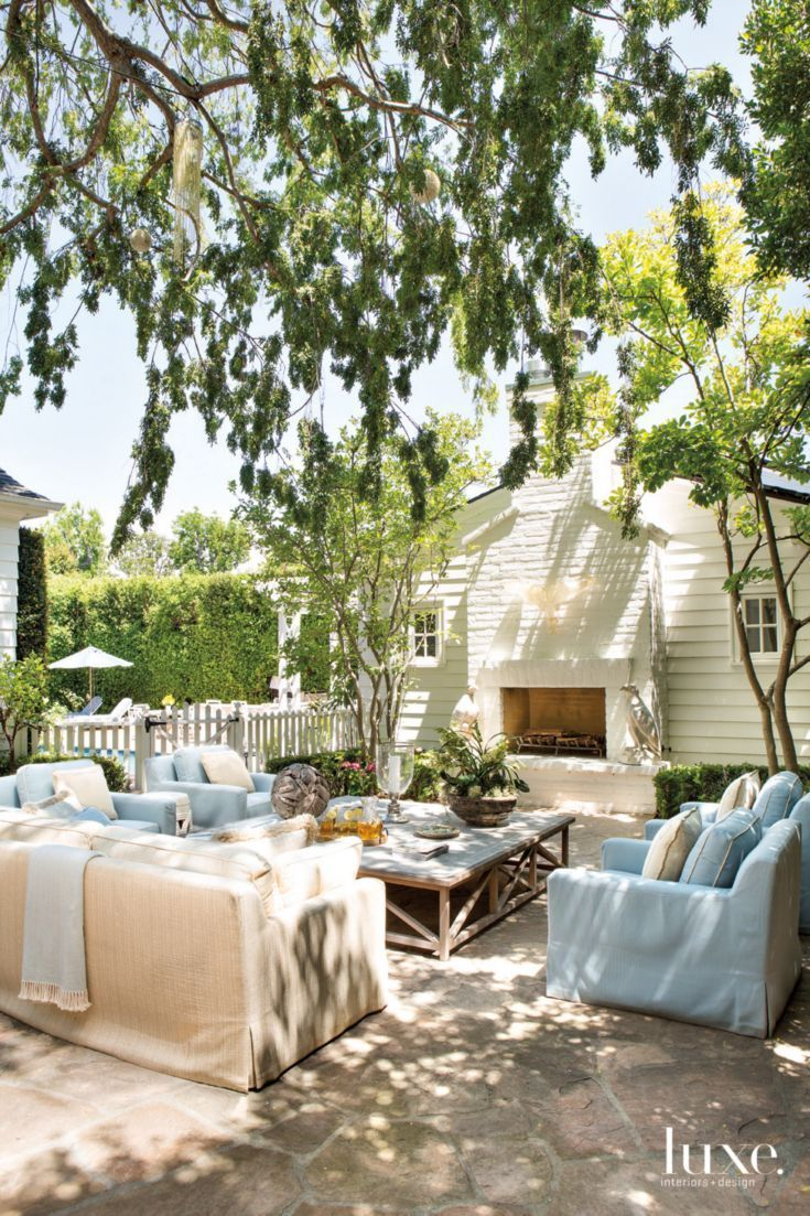 Beautiful cottage patio with light blue and white outdoor furniture.