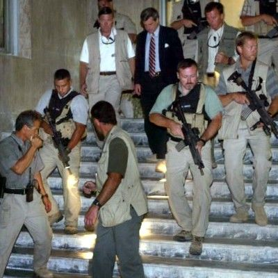October 13, 2003: Escorted by Blackwater 'security guards', Paul Bremer -- head of the Coalition Provisional Authority -- walks down the steps of the Al Hamar hotel after a night-time meeting in Baghdad