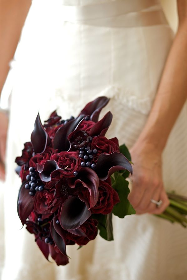 Burgundy bridal bouquet with calla lilies, roses, chocolate cosmos and berries.
